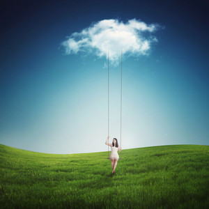 A woman is on a swing hanging from a single cloud