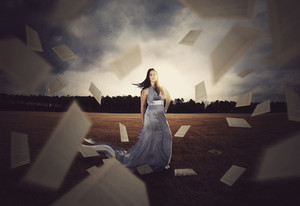 A woman is surrounded by a storm of book pages