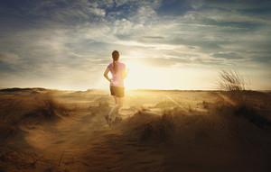 A woman jogs through the sandy desert