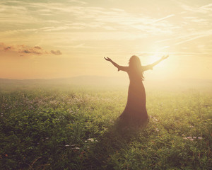 A woman lifts her arms in praise at dawn