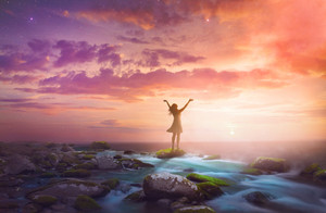 A woman lifts her arms in praise at sunrise