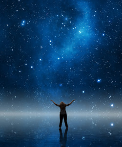 A woman lifts her arms out in praise under the night sky