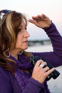A woman looking at something off in the distance with binoculars in her hands while at the seashore.