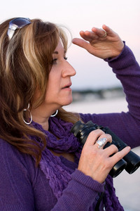 A woman looks at something off in the distance with binoculars in her hands while at the seashore.
