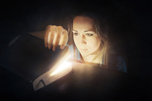 A woman looks inside a Bible that is glowing