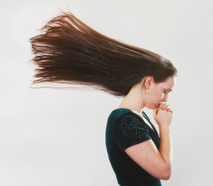 A woman praying and her is hair flying backwards.