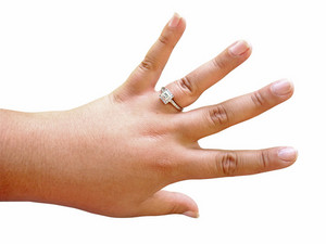 A woman proudly showing off her custom made engagement ring - isolated over white.  Image includes clipping path.