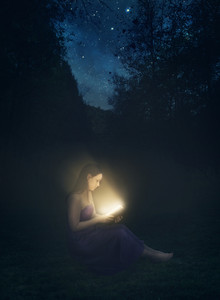 A woman reading a glowing book at night.