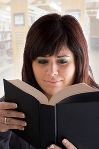 A woman reads a black hardcover book at the library.  Shallow depth of field.