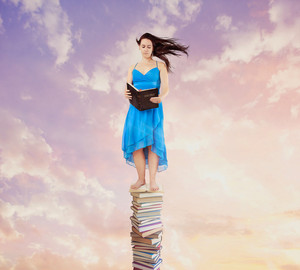 A woman reads her Bible while standing on a tall stack of books