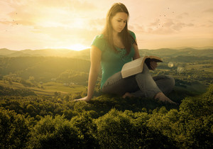 A woman sits on the landscape as she studies her Bible