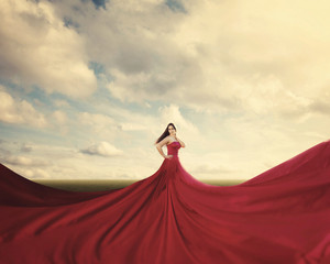 A woman standing in a field with a huge red dress.