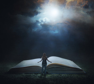 A woman stands in front of a large Bible in a field