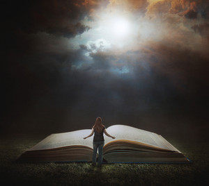 A woman stands in front of a large Bible
