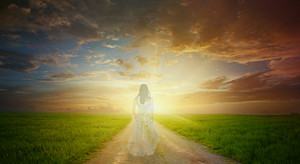 A woman that is tranparent walks the path to the bright sunlight