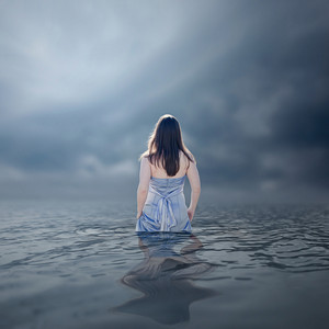 A woman wades into deep waters