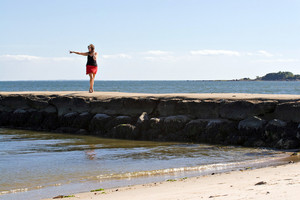 A woman walks down the jetty at the beach pointing to something in the distance.