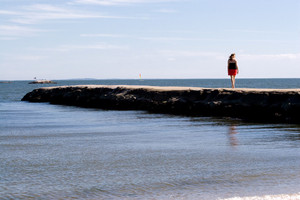 A woman walks down the jetty at the beach.