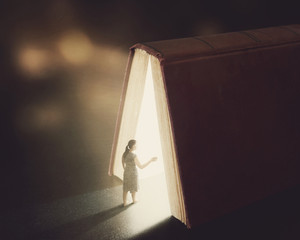 A woman walks into the pages of glowing Bible