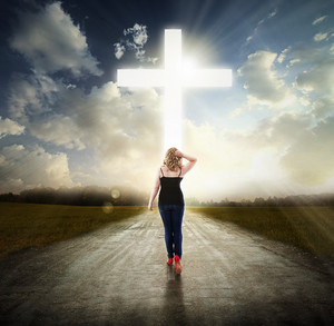 A woman walks on a road towards the cross