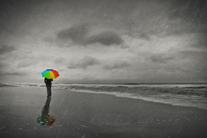 A woman walks on the beach with a colorful umbrella