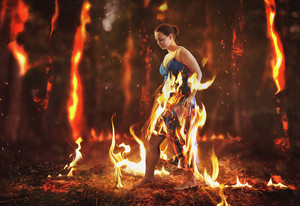 A woman walks through a burning forest fire
