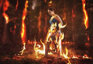 A woman walks through a burning forest fire