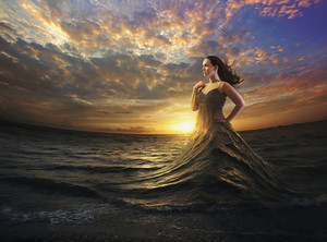 A woman wears the ocean as a dress.