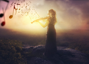 A woman with a violin playing music at sunrise.