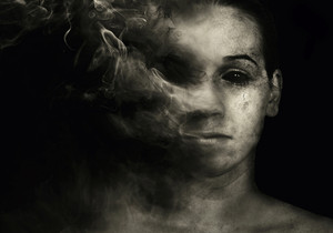 A woman's face disappears into smoke