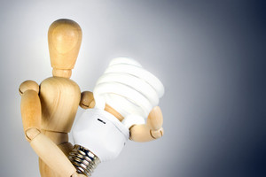 A wooden model grasping a compact fluorescent light bulb.  Great for energy savings or going green concepts.