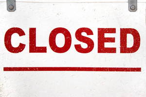 A worn and grungy looking closed sign with red letters painted onto a white background.