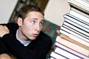 A worried student looks up at the high pile of textbooks he has to go through to do his homework assignment.