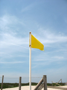 A yellow caution flag posted in the sand at the beach.