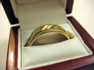 A yellow gold mens wedding band inside its box.