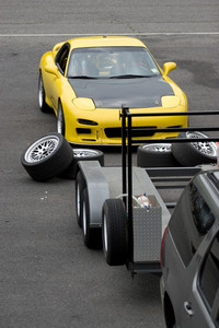 A yellow sports car in the race track pit area.