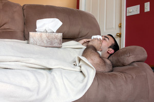 A young adult sick on the couch at home blows his nose with a tissue.