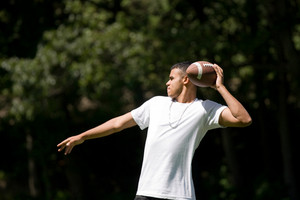 A young adult throwing a football outside.