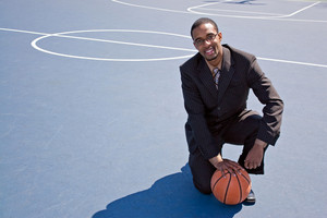 A young African American man in a business suit posing on the basketball court with a ball.  Works great for coaching or recruitment concepts.