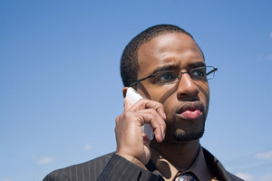 A young African American man talking on his cellular phone with a concerned or serious look on his face.
