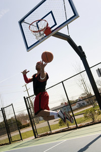 A young athlete driving to the basketball hoop for a lay up or slam dunk.
