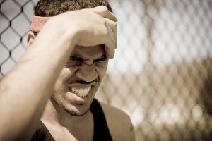 A young athlete grabs his forehead in anger or pain.