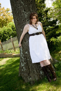 A young attractive woman in a white dress leaning against a tree trunk.