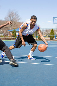 A young basketball player dribbling the ball past the competition.