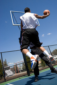 A young basketball player driving to the hoop with some fancy moves during a one on one game at the park.