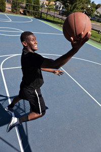 A young basketball player driving to the hoop with some fancy moves. Shallow depth of field.