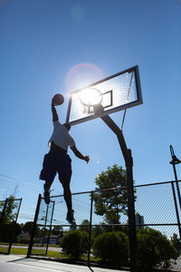 A young basketball player going up for a dunk.  Intentionally back lit with bright lens flare coming through the clear backboard.