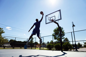 A young basketball player going up for a layup.  Intentionally back lit with bright lens flare.