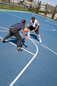 A young basketball player guarding his opponent during a one on one basketball game.