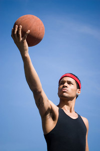 A young basketball player holding the ball up to the sky.